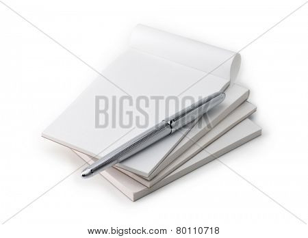 Stack of blank memo pads in real use condition, with a silver pen, isolated on white.