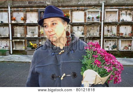Woman With Flowers At The Cemetery