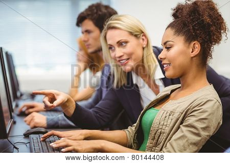 Attractive teacher talking to her student in computer class at the university poster