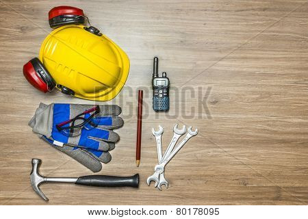 Background of personal safety accessories on a wooden surface. Items include a hard hat with ear protection attached, safety goggles, working gloves, a hammer, wrenches, pencil and a cb radio