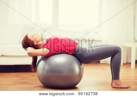 fitness, home and diet concept - smiling redhead girl exercising with fitness ball at home poster