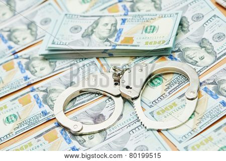 money bribe or corruption theme. handcuffs lying on dollars banknotes poster