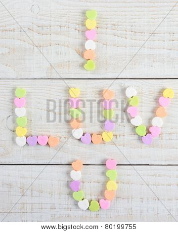 High angle shot of a  group of pastel candy Valentine's hearts forming I Luv U on a rustic white wood table.