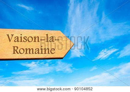Wooden arrow sign pointing destination Vaison-la-Romaine FRANCE against clear blue sky with copy space available. Travel destination conceptual image poster