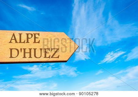 Wooden arrow sign pointing destination ALPE D'HUEZ FRANCE against clear blue sky with copy space available. Travel destination conceptual image poster