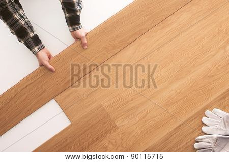 Top quality wooden floor installation at home carpenter's hands placing a tile on the floor top view poster