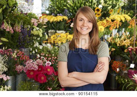 Florist Standing In Shop In Front Of Flower Display