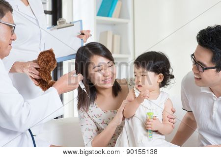 Child vaccination. Family doctor vaccines or injection to baby girl. Pediatrician and patient.