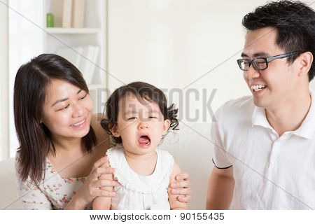 Parents is comforting their crying daughter. Asian family at home.