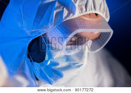 science, chemistry, biology, medicine and people concept - close up of scientist face in goggles and protective mask at chemical laboratory