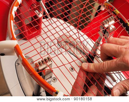 Racquet stringer weaving cross strings on a Tennis racquet stringing machine