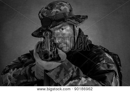 Soldier in camouflage and modern weapon M4 on black background poster