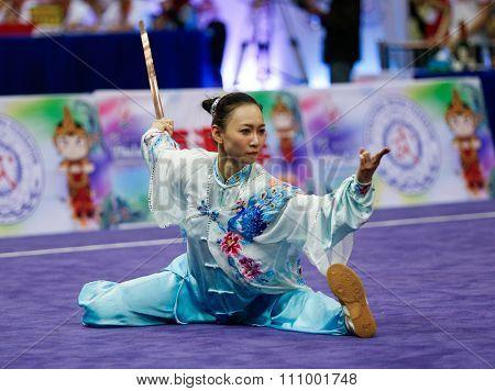 JAKARTA, INDONESIA - NOVEMBER 15, 2015: Shin Ng of Malaysia performs the movements in the women's Taijijian event at the 13th World Wushu Championship 2015 held at Istora Senayan, Jakarta.