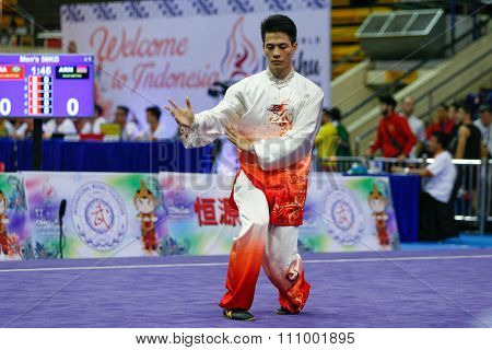 JAKARTA, INDONESIA - NOVEMBER 15, 2015: Zhou Li Chen of China performs the movements in the men's Taijiquan event at the 13th World Wushu Championship 2015 held in Istora Senayan, Jakarta.