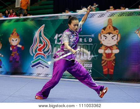 JAKARTA, INDONESIA - NOVEMBER 15, 2015: Kariza Kris Chan of Philippines performs the movements in the women's Shuangjian event at the 13th World Wushu Championship 2015 held in Istora Senayan.