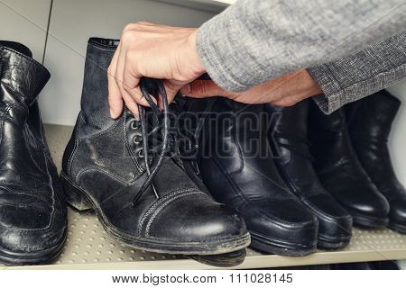 closeup of a young caucasian man picking a pair of leather boots from the closet
