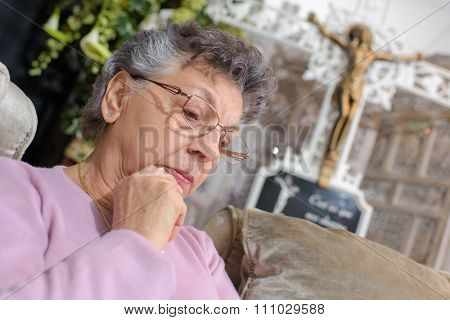 elderly woman in front of crucifix