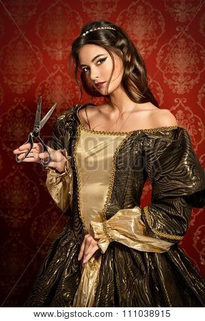 Beautiful young woman in a lush renaissance dress posing with tailoring scissors. Vintage background. Fashion history. Haute Couture.