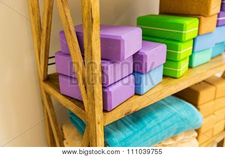 yoga, sport, fitness and objects concept - close up of wooden rack with yoga foam blocks and fleece plaids stored on it