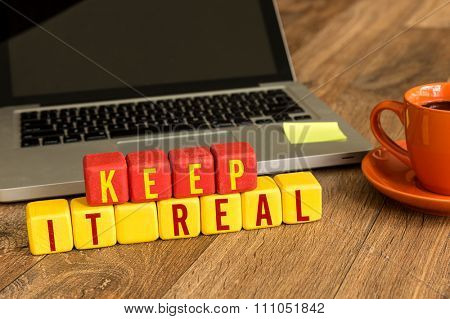 Keep it Real written on a wooden cube in a office desk