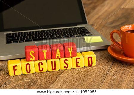 Stay Focused written on a wooden cube in a office desk