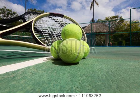 Tennis balls and racquets on the court close-up