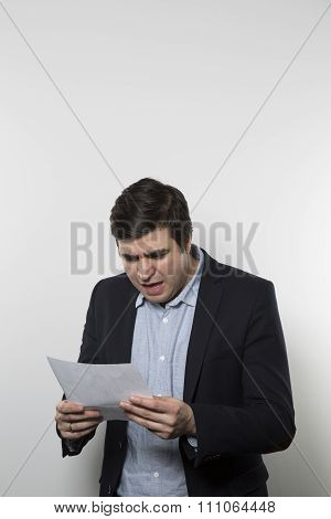 studio shot of angry businessman reading a paper