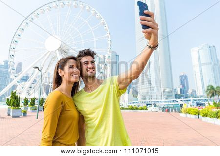 Caucasian couple take the selfie by sellphone at Hong Kong