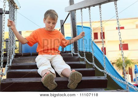 Caucasian Boy In Orange Shirt Sitting On Suspension Bridge On Playground, Hands On Chains