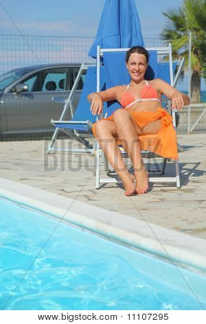 Young Woman In Orange Bikini And Pareo Sitting On Beach Chair