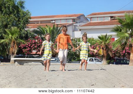 Little Boy And Two Girls Walking On Beach, Holding For Hands, Front View, Palms And Building