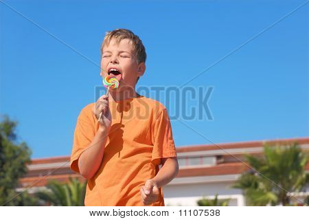 Little Boy In Orange Shirt Licking Multicolored Lollipop, Closed Eyes, Palms And Building