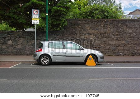 Car Street Clamped With Yellow Metal Wheel Clamp. Trees Grow Behind Wall