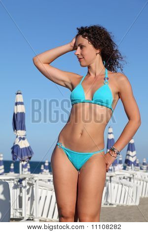 Beautiful Young Woman In Blue Swimsuit Stands On Beach, Rows Of White Deck Chairs And Beach Umbrella