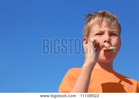 Little Boy In Orange Shirt Eating Multicolored Lollipop, Blue Sky