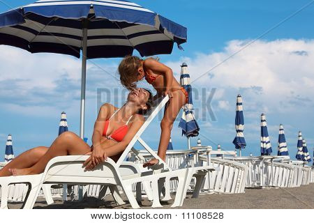 Young Mother Lying On Lounger Under Beach Umbrella. Little Daughter Standing Near Mother