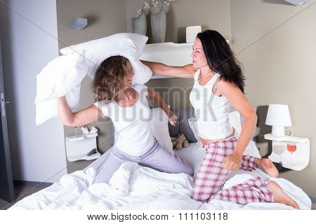 Two Attractive Women In Bed Having A Pillow Fight
