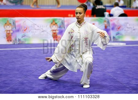 JAKARTA, INDONESIA - NOVEMBER 16, 2015: Barbara El Rassi of Lebanon performs her movements in the Women's Compulsory Taijiquan event at the 13th World Wushu Championship 2015 in Jakarta.