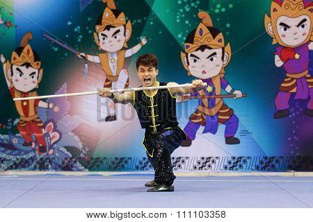 JAKARTA, INDONESIA - NOVEMBER 16, 2015: Jun Hua Huang of Macao performs the movements in the Men's Nangun event at the 13th World Wushu Championship 2015 at the Istora Senayan Stadium.