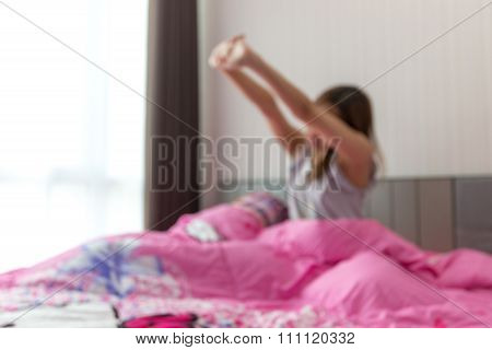 Woman stretching in her bed, un-focus