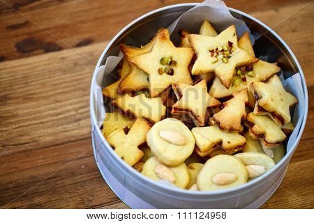 Freshly baked homemade Christmas cookies in a tin box, wooden background