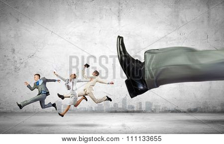 Big businessman foot kicking businesspeople running away