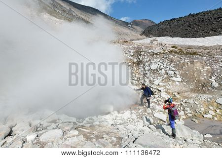 Tourists standing by smoking fumaroles on crater active volcano. Kamchatka, Russia, Eurasia