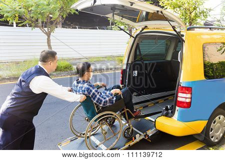 Driver Helping Man On Wheelchair Getting Into Taxi