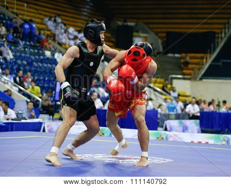 JAKARTA, INDONESIA - NOVEMBER 16, 2015: Mohsen Mohammadseifi of Iran (red) fights Van Tai Nguyen of Vietnam (black) in the men's 70kg Sanda event at the 13th World Wushu Championship 2015.