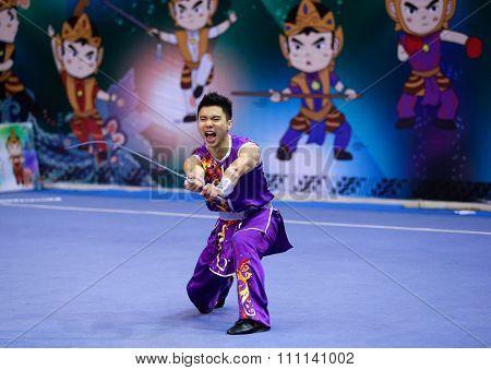 JAKARTA, INDONESIA - NOVEMBER 16, 2015: Cheuk Hei Leung of Hong Kong  performs the movements in the men's Nandao event at the 13th World Wushu Championship 2015 at the Istora Senayan Stadium.
