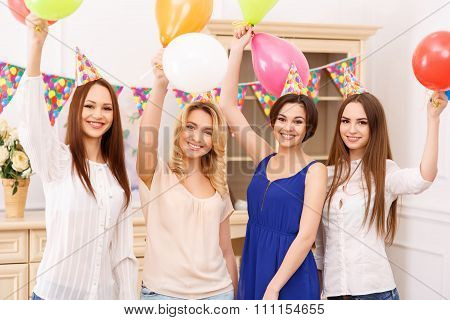 Young girls holding colorful balloons