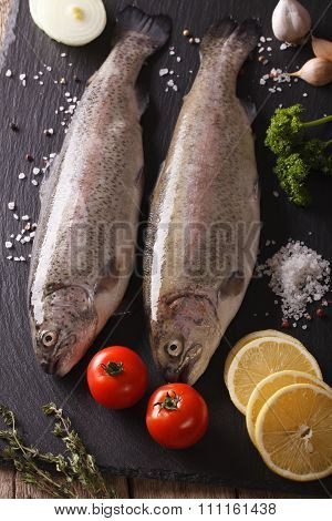 Raw Rainbow Trout With Ingredients On A Slate Board Closeup. Vertical