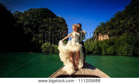 Groom Blonde Bride In Fluffy Stand On Nose Of Longtail Boat