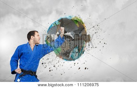 Young determined karate man breaking with leg concrete Earth planet. Elements of this image are furnished by NASA